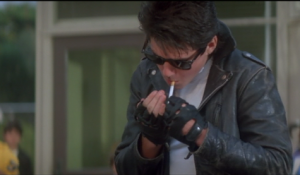 Greased hair, sunglasses, a black leather jacket, and smoking. The full package of cool.